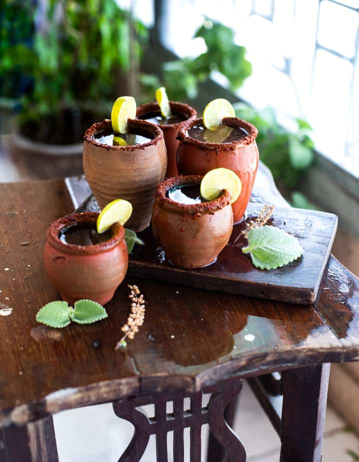 Tamarind Margarita in clay glasses with lemon slices