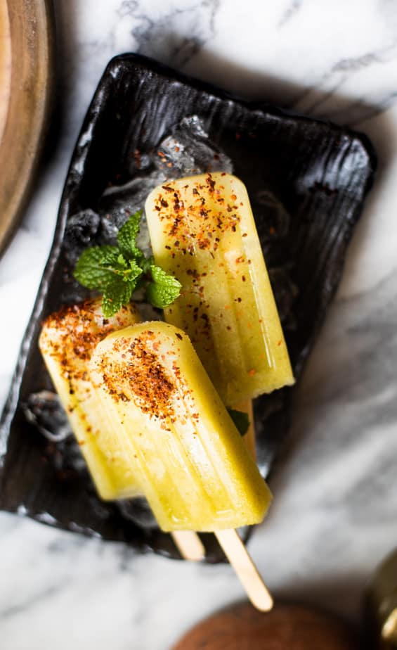 Green mango popsicles sprinkled with Aleppo pepper on a rectangular plate