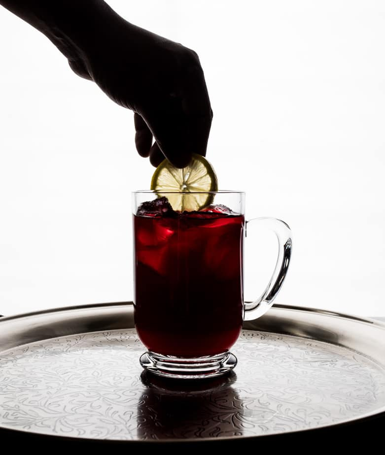 cranberry based cocktail with a Lemon Slice