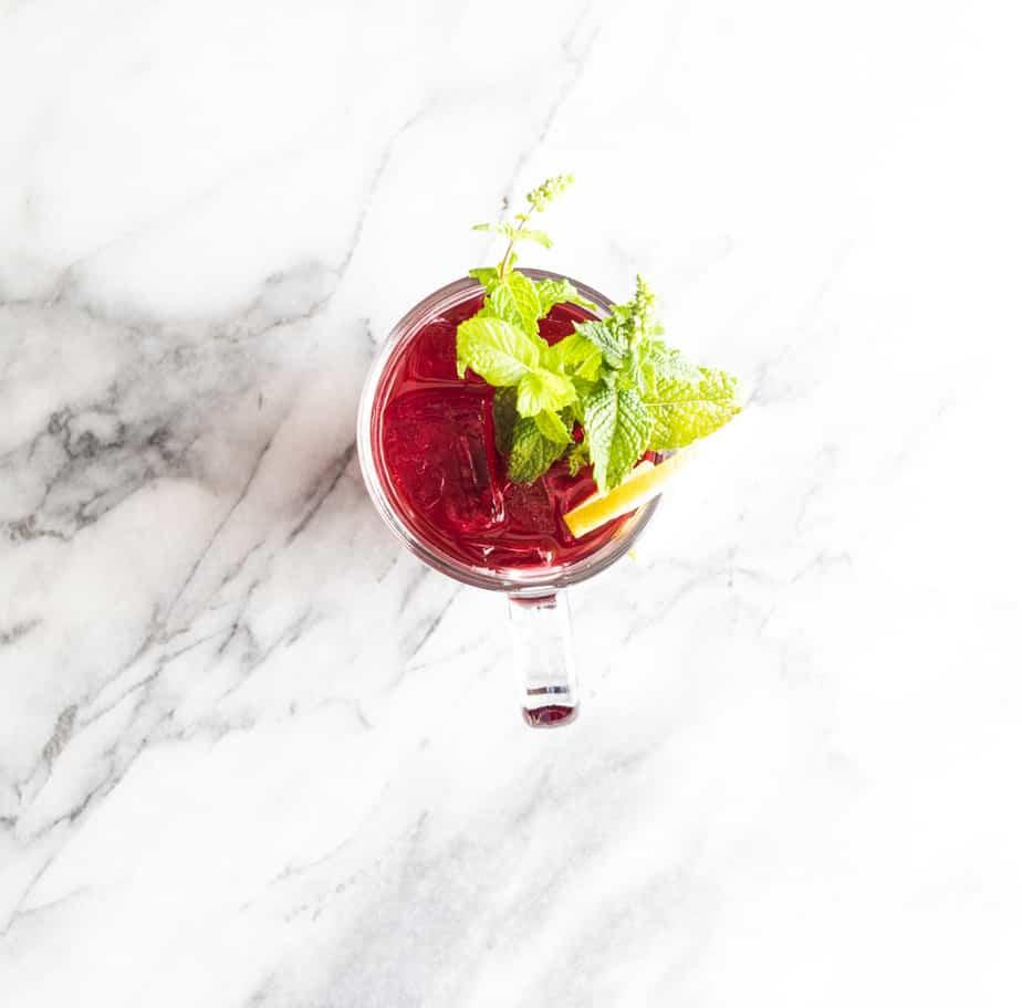 Lemon slice, mint flowers in a cranberry vodka cocktail.