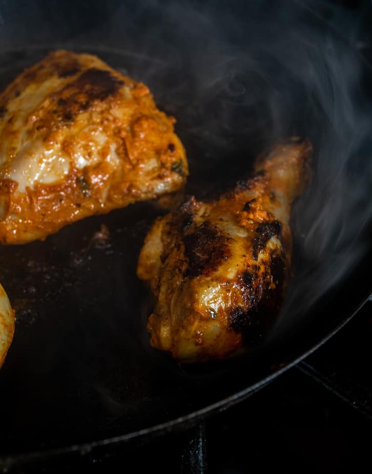 Chicken pieces being seared along with the tikka masala marinade.